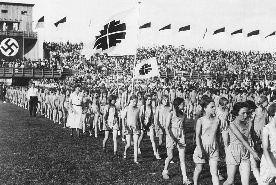 図5.シュトゥットガルトのドイツトゥルネン祭(1933年)における少女たちの行進。来賓席の背後にはナチ党のハーケンクロイツの旗が掲げられている。 SPORT : SCHAU. Deutsche Turnfeste 1860-2002, Leipzig 2002