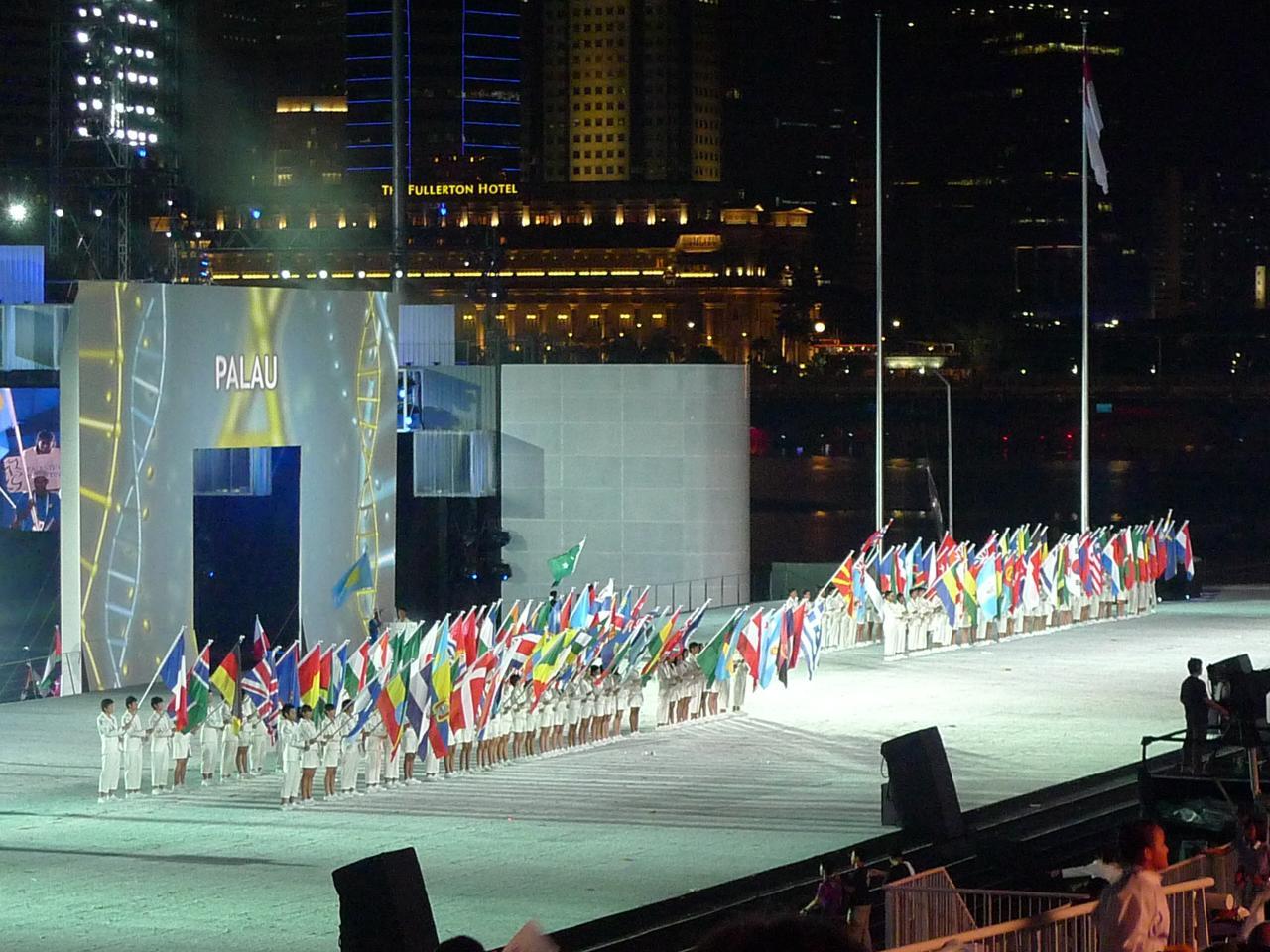 図6.選手団の旗。マリーナ湾フローティングプラットフォームで開かれたユースオリンピック大会(2010年)の開会式にて。 https://www.en.wikipedia.org/wiki/2010_Summer_Youth_Olympics#/media/File:Opening_Ceremony_of_Singapore_YOG_2010_flags.jpg